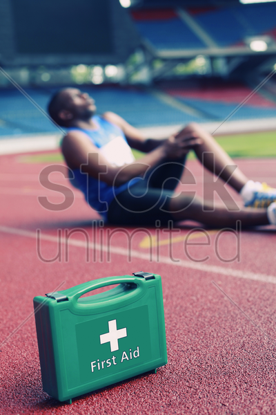 first aid kid, male athlete clasping leg in pain in the background stock photo