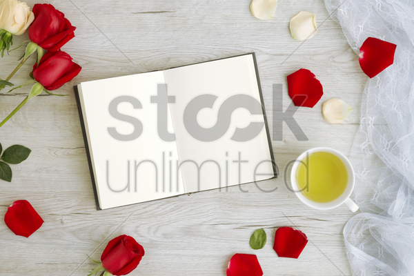 flatlay of wooden background with roses and journal stock photo