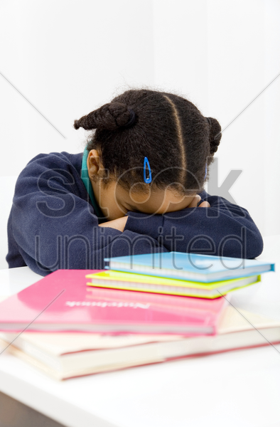 girl sleeping with her head on the table stock photo
