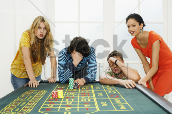 group of friends losing on roulette table stock photo
