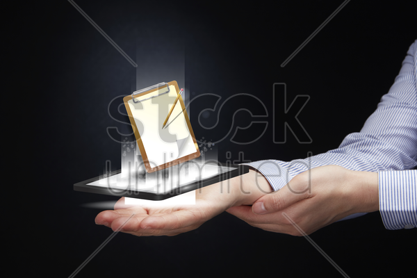 hand presenting tablet projecting clipboard stock photo