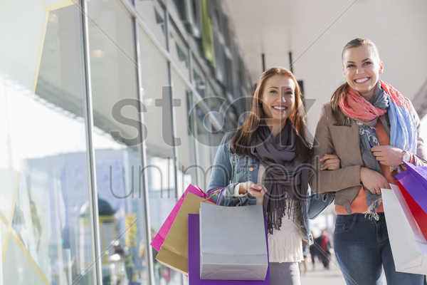 happy female friends with shopping bags walking by store stock photo