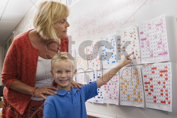 little boy pointing to a calendar date for teacher stock photo