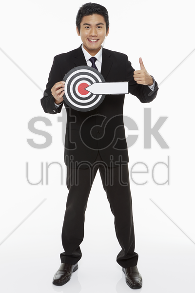 man holding up a dart board, giving thumbs up stock photo