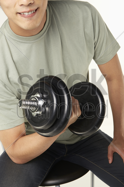 man lifting dumbbells stock photo