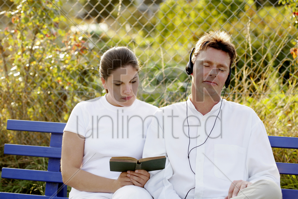 man listening to music on the headphones while his wife is reading book stock photo