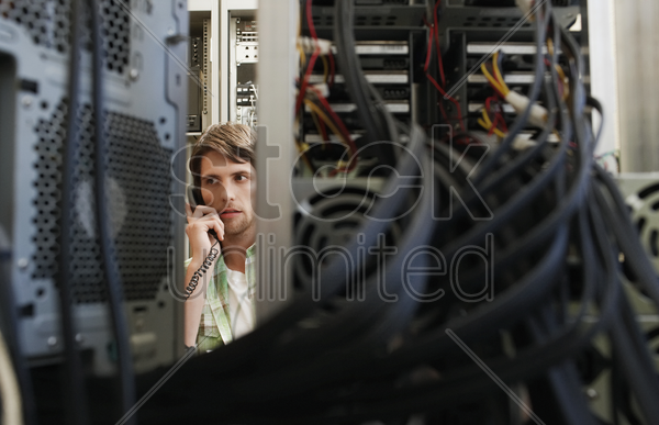 man using phone surrounded by computer equipment stock photo