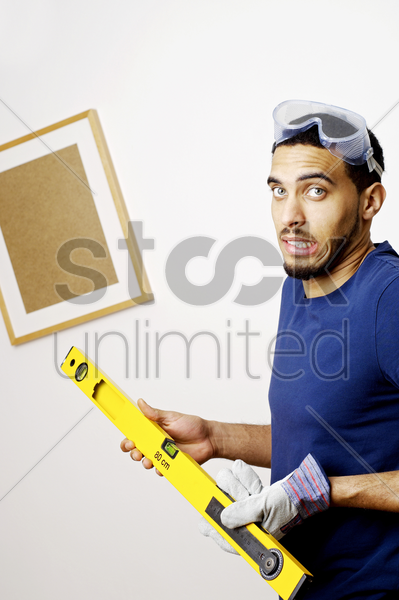 man with goggles holding a spirit level stock photo