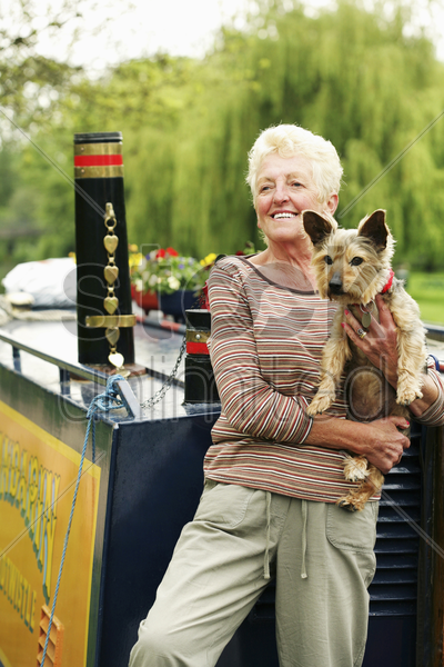 senior woman posing with her dog on the houseboat stock photo