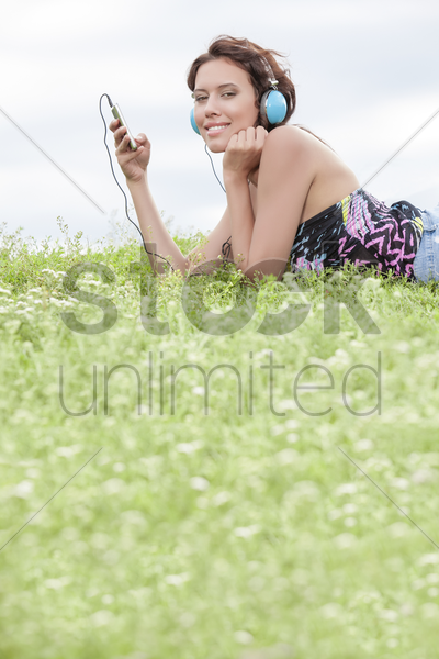 side view portrait of woman listening to music through cell phone using headphones while lying on grass against sky stock photo