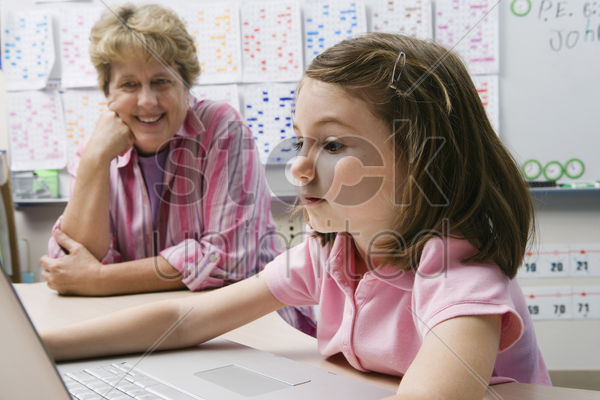 teacher watching schoolgirl use laptop stock photo