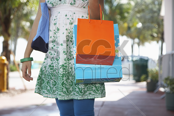 teenage girl (16-17) carrying shopping bags walking on street mid section stock photo