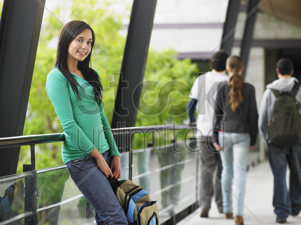 teenage girl leaning against railing in corridor portrait stock photo
