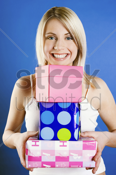 woman carrying a stack of presents stock photo