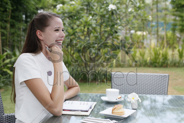 woman contemplating, organizer and breakfast on the table stock photo