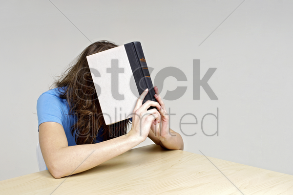 woman covering her face with a book stock photo