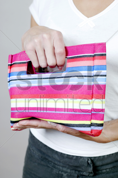 woman holding a striped bag stock photo