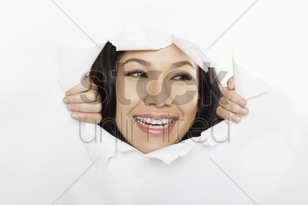woman looking through a torn paper stock photo