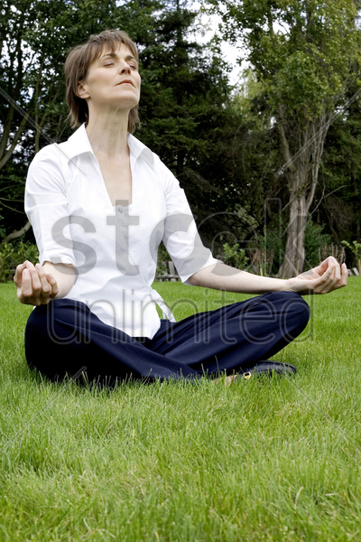 woman meditating in the park stock photo
