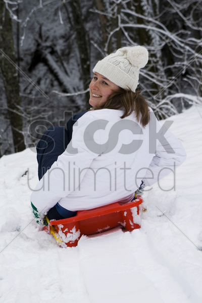 woman snow sliding stock photo