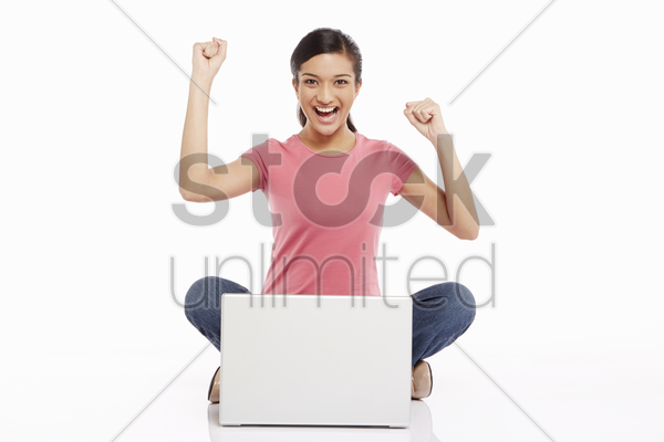 woman using laptop and cheering stock photo