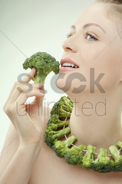 woman with a string of broccoli around her neck stock photo