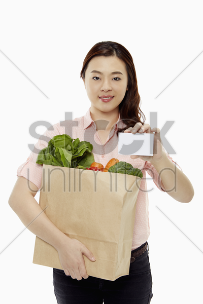 woman with groceries holding up a blank card stock photo