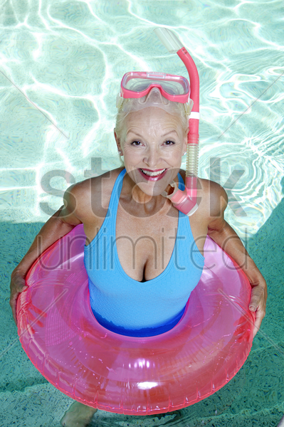 woman with snorkeling goggles and inflatable ring standing in the swimming pool stock photo