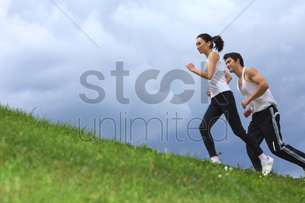 young couple exercising in park stock photo