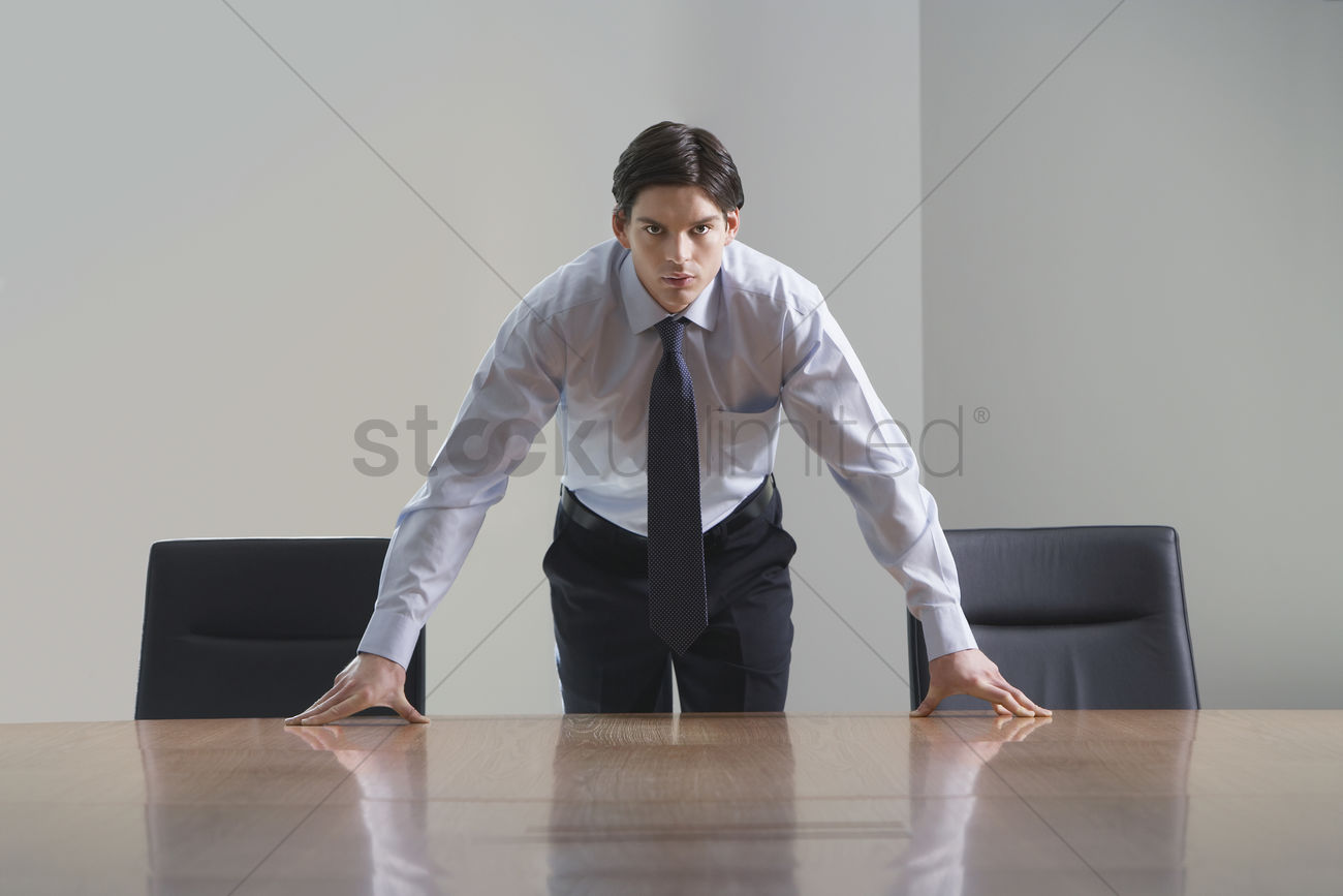 Businessman Standing And Leaning Over Conference Room Table Stock - Standing conference room table