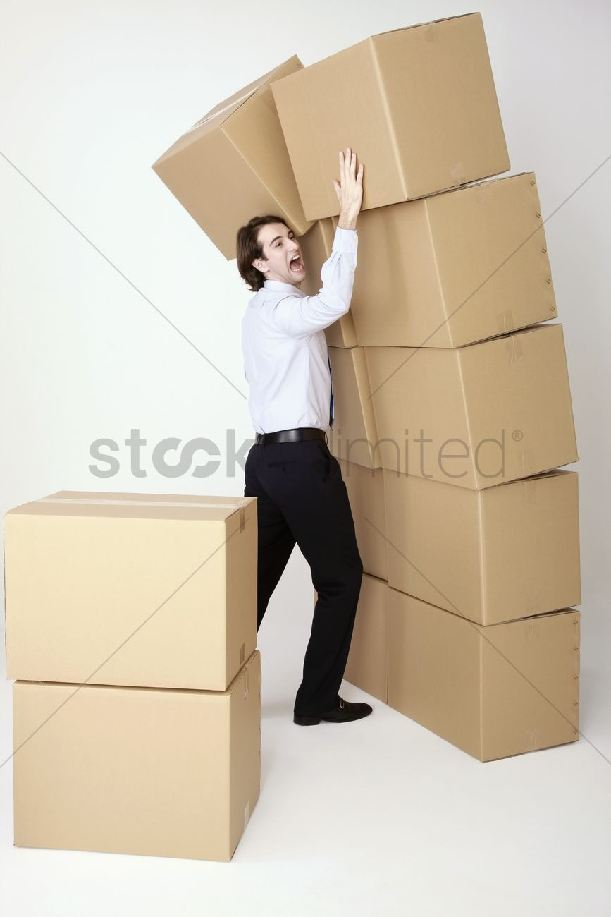 businessman stopping stacked boxes from falling down stock photo