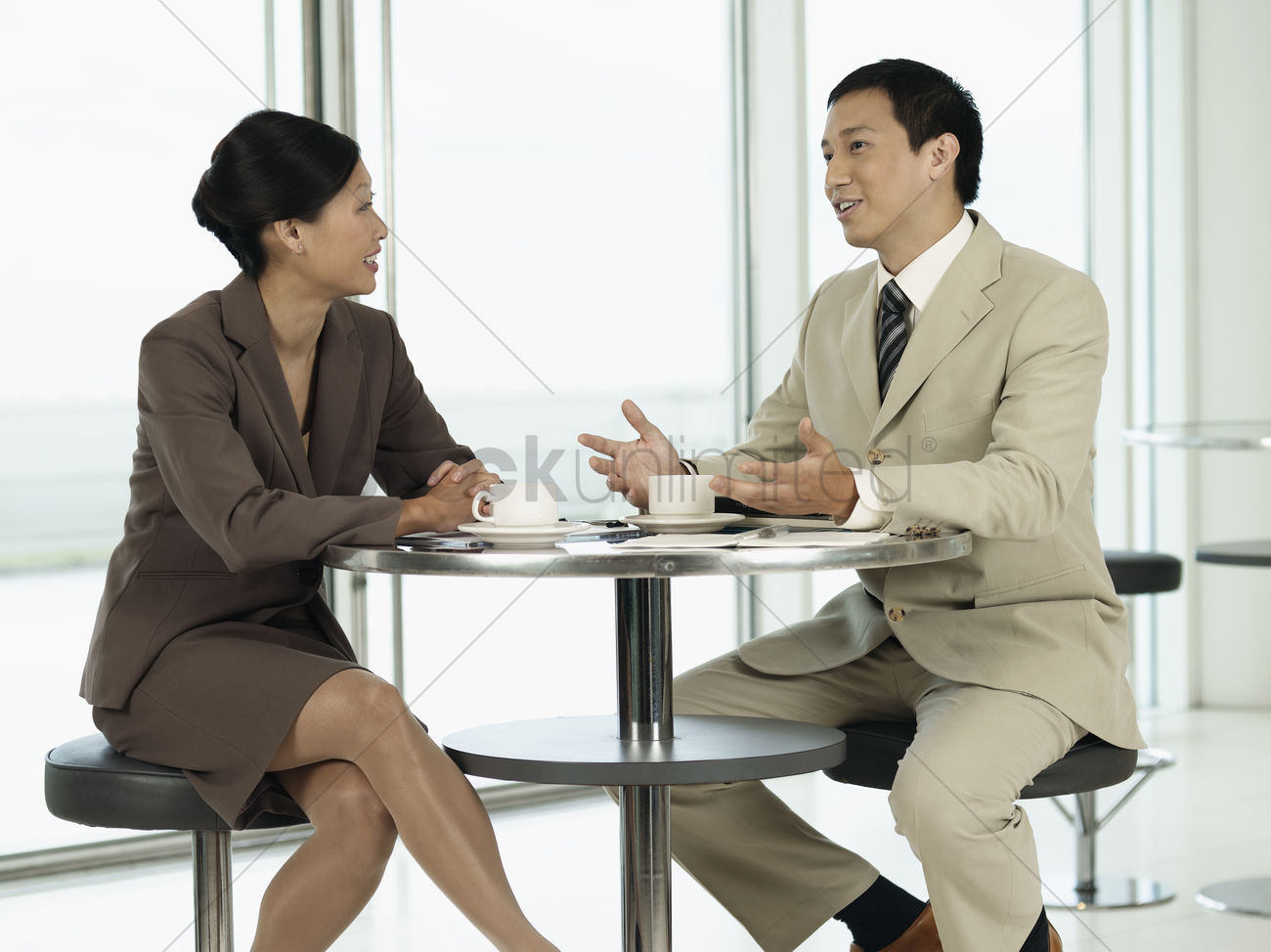 businesspeople sitting at table talking to each other stock photo