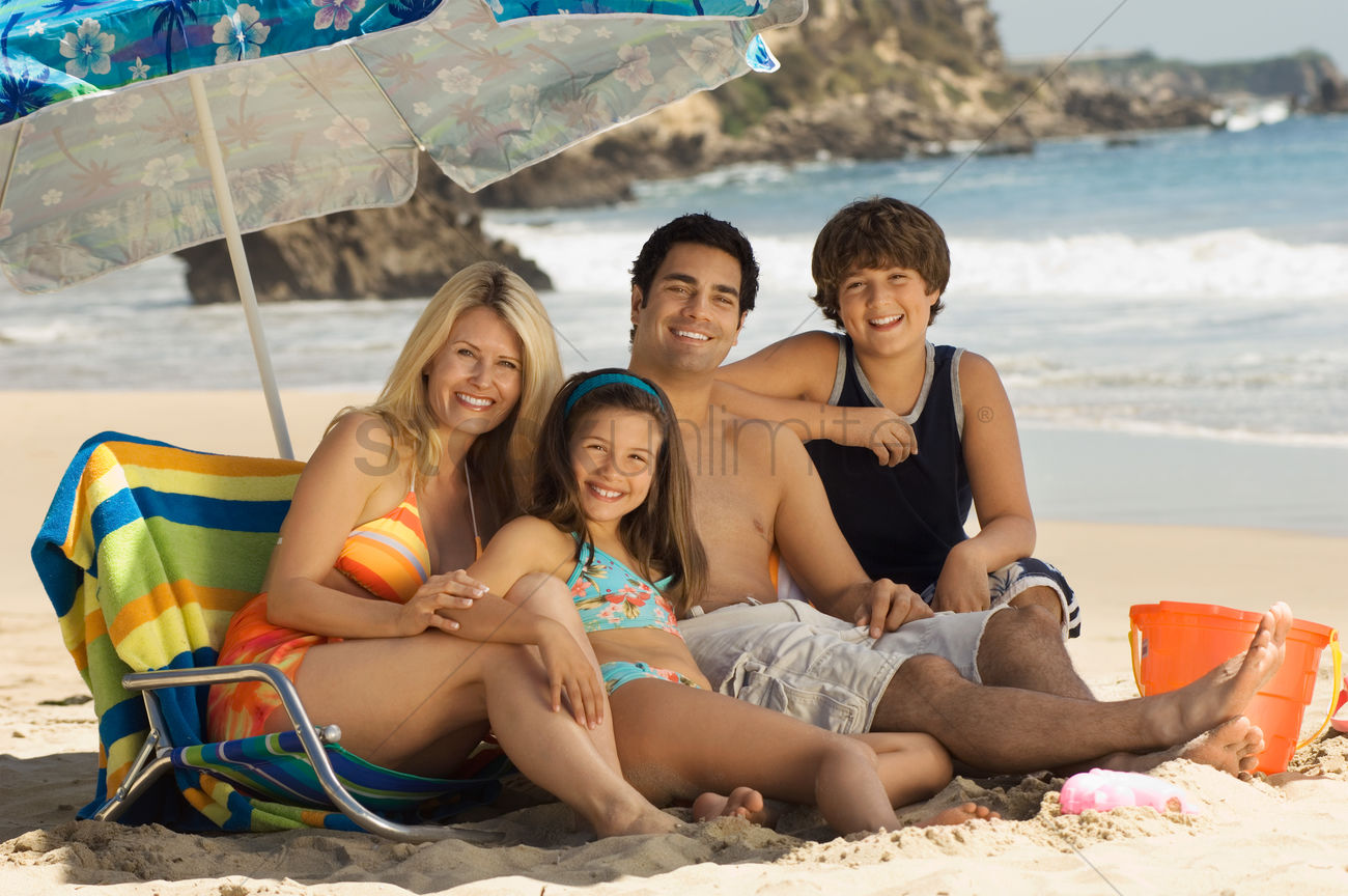 Family In Swimwear On Beach Sitting On Lounge Chair Under Parasol Portrait Stock Photo 1878425 Stockunlimited