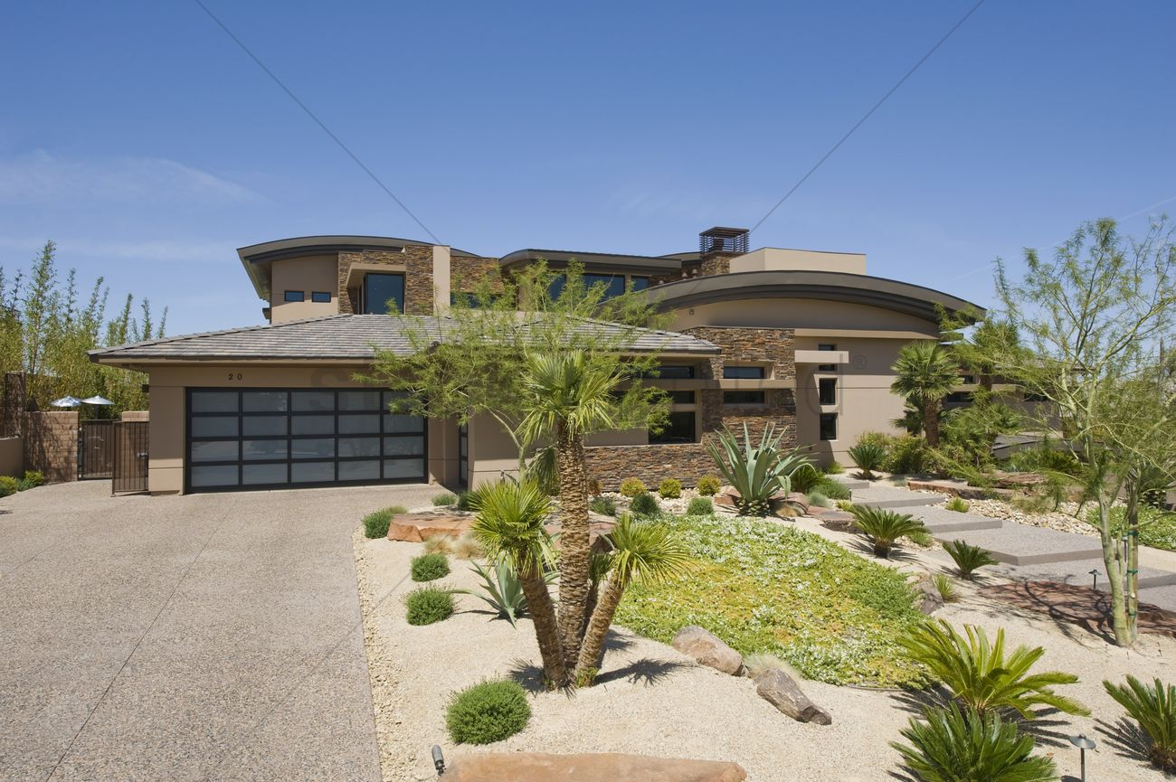house exterior with a driveway plants trees and a path stock photo