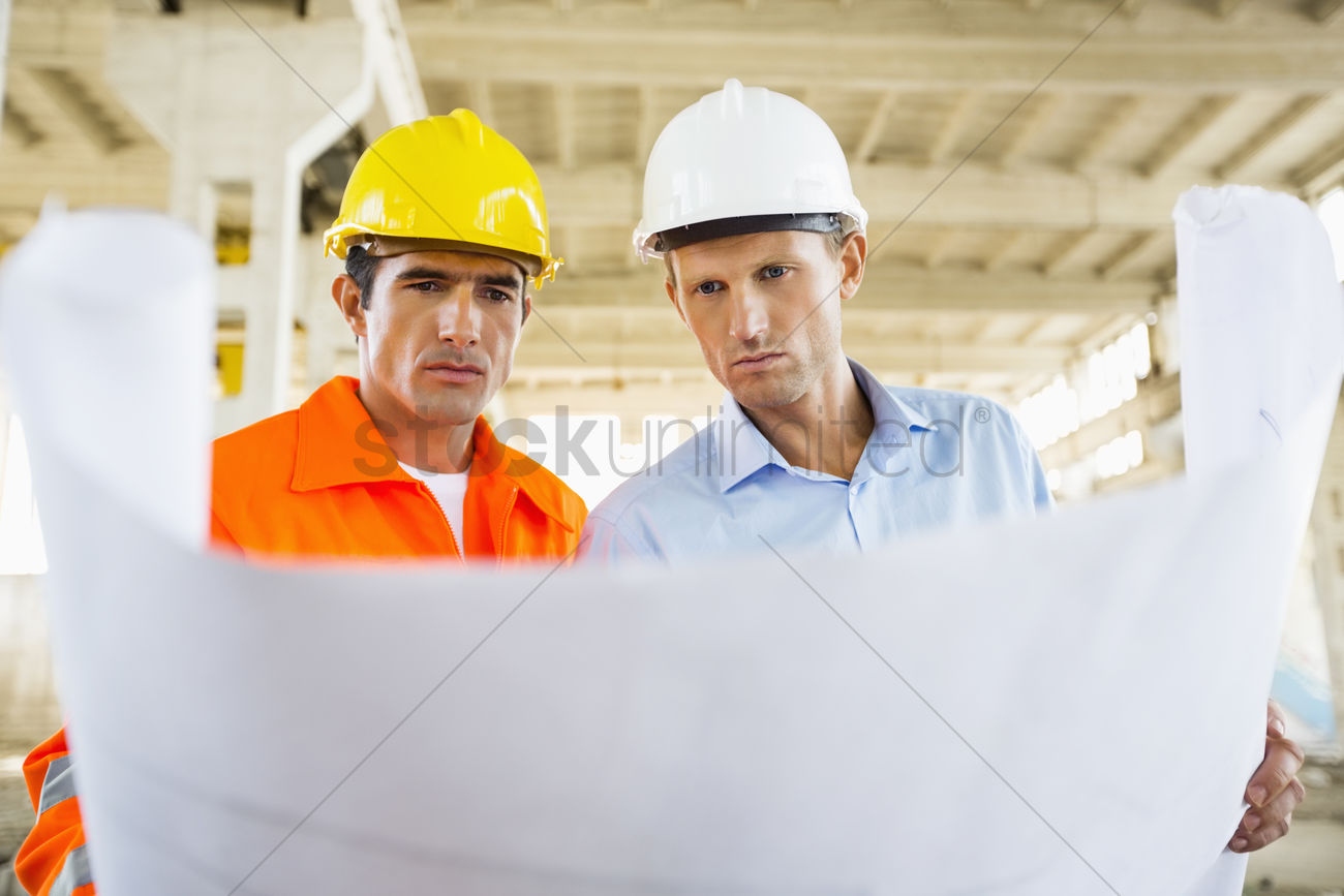 Male architects reviewing blueprint at construction site stock photo male architects reviewing blueprint at construction site stock photo malvernweather Image collections