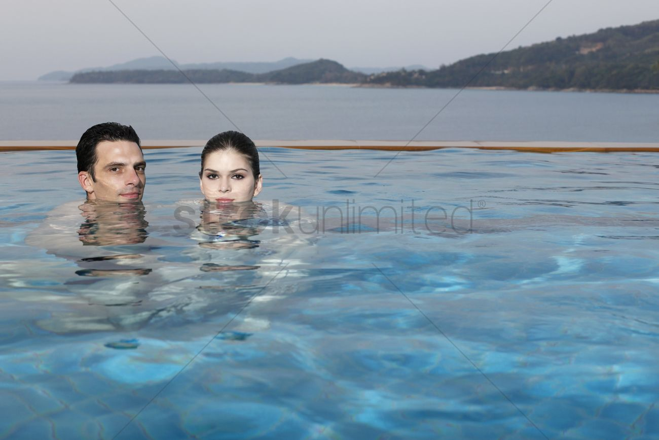 Man and woman in pool, heads half submerged in water Stock Photo ...