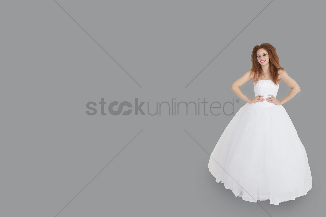 0039ca2c93528 portrait of happy brunette in wedding dress with hands on hips standing  over gray background stock