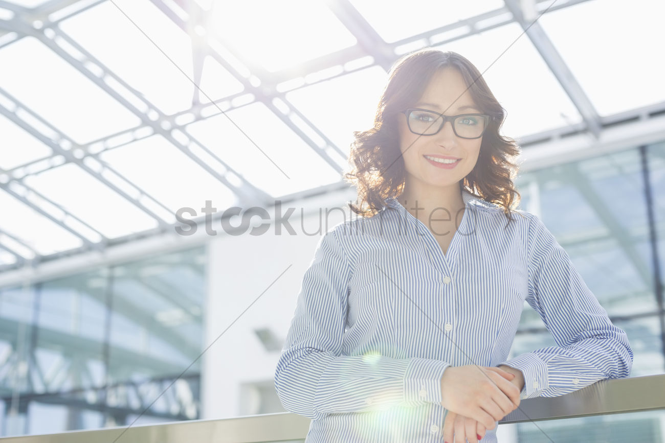 portrait of happy young businesswoman leaning on railing in office