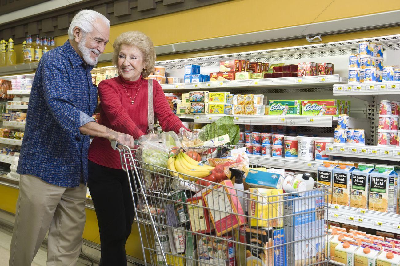 Senior Couple Food Shopping In Supermarket Stock Photo