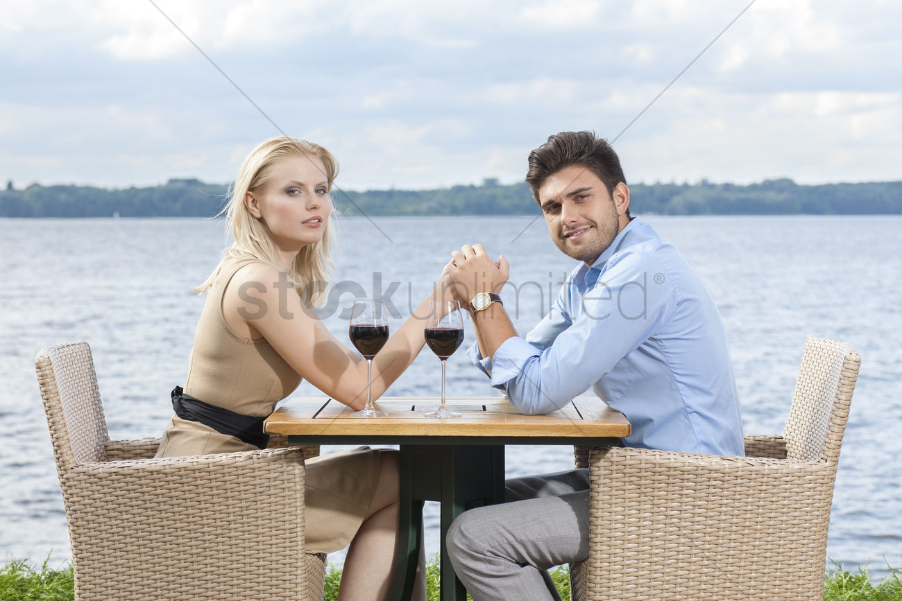 Side View Portrait Of Young Couple Holding Hands At Outdoor Restaurant By Lake Stock Photo 1927397 Stockunlimited