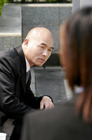 A bald man in business suit looking at a girl