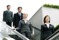 A group of business people coming down from an escalator