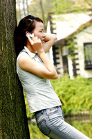 A lady leaning against a tree talking on the hand phone
