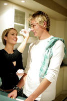A lady putting some foam on her boyfriend s nose