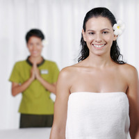 A siamese massage therapist welcoming her customer to the resort spa