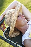 A woman in a straw hat sleeping on a rest chair