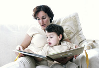 A woman sitting on the couch reading a book for her son