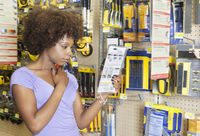 African american woman reading instructions on a product at super market