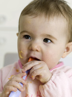 Baby girl with food on face biting on a plastic spoon