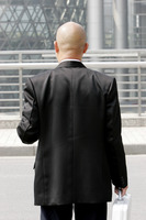 Back shot of a bald man in business suit